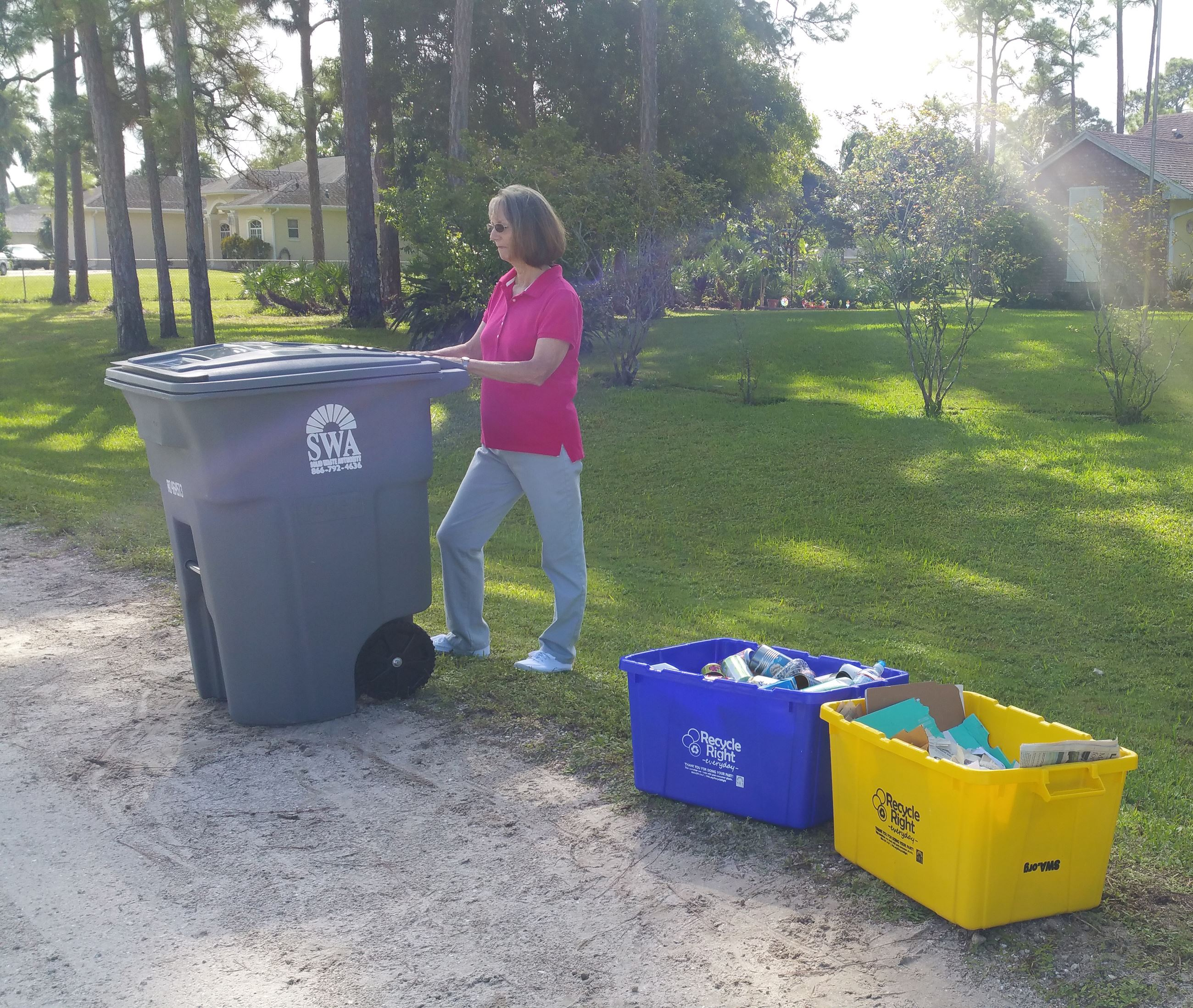 Woman wheeling 95 gallon garbage cart to curb with recycling bins